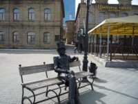 Скульптура горожанина на лавочке между театром и фонтаном.